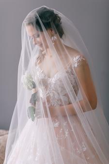 Portret piękna panna młoda w białej rocznik sukni z kwiatem w jej rękach pozuje pod przesłoną na szarości ścianie