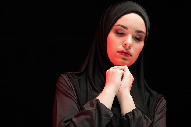 Portret piękna poważna młoda muzułmańska kobieta jest ubranym czarnego hijab