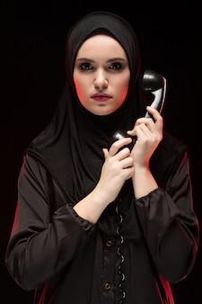 Portret piękna poważna okaleczająca młoda muzułmańska kobieta jest ubranym czarnego hijab