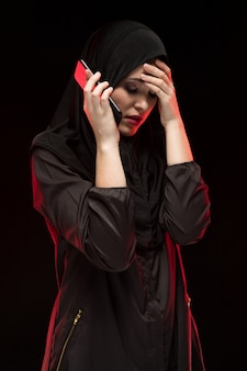 Portret piękna poważna okaleczająca przestraszona sfrustowana młoda muzułmańska kobieta jest ubranym czarnego hijab dzwoni o pomoc na czarnym tle
