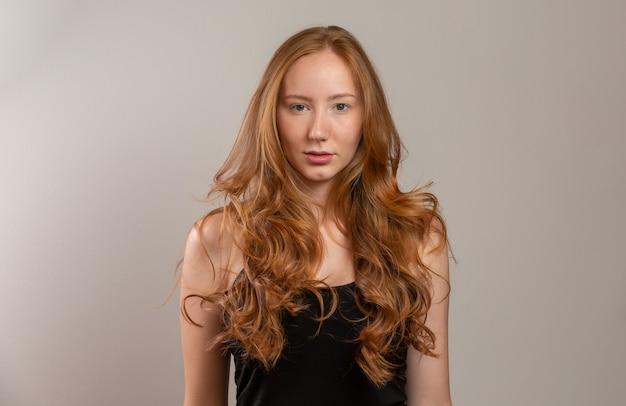 Portret piękna rozochocona rudzielec dziewczyna ono uśmiecha się śmiać się nad biel ścianą