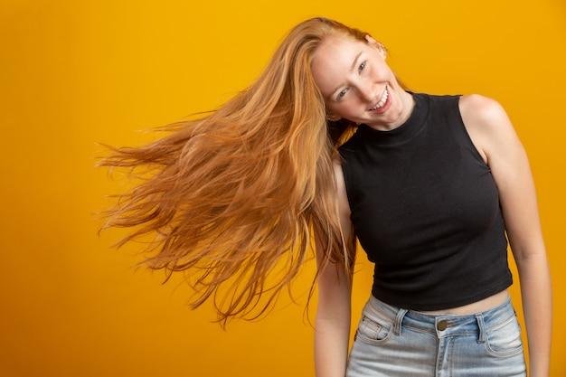 Portret piękna rozochocona rudzielec dziewczyna z latającym włosy ono uśmiecha się śmia się nad kolor żółty ścianą.
