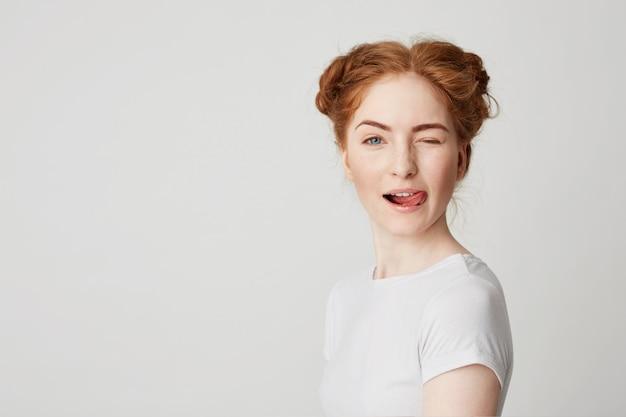 Portret piękna rudzielec dziewczyna ono uśmiecha się pokazywać jęzoru mrugać.