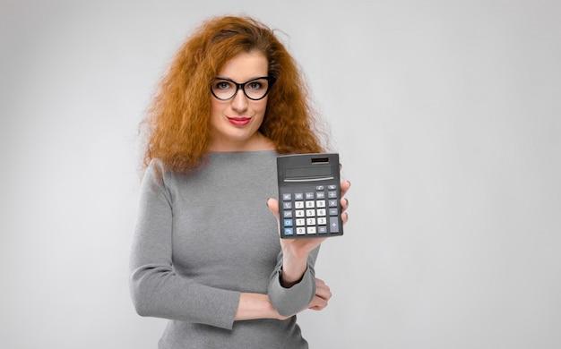 Portret piękna rudzielec młoda kobieta w szarość odziewa w szkłach pokazuje kalkulatora na szarości ścianie