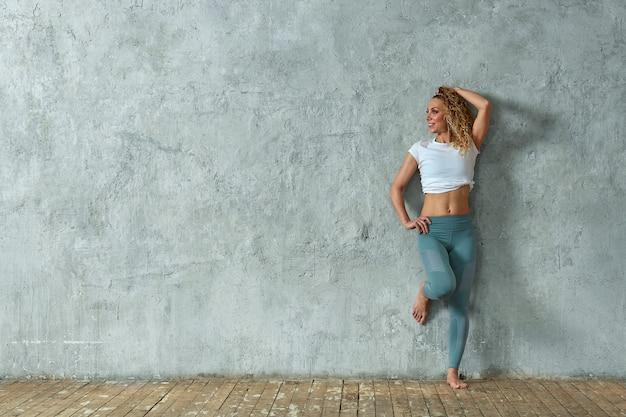 Portret piękna seksowna blondynki dziewczyna ono uśmiecha się, na szarym tle