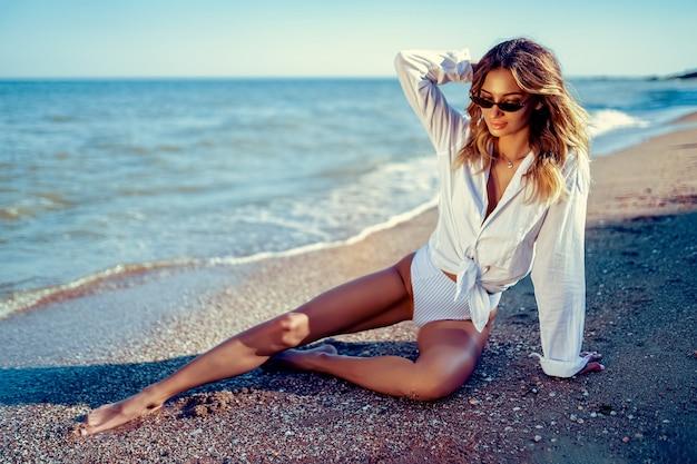 Portret piękna seksowna caucasian sunbathed kobieta w okularach przeciwsłonecznych z długie włosy w swimsuit lying on the beach na lato plaży