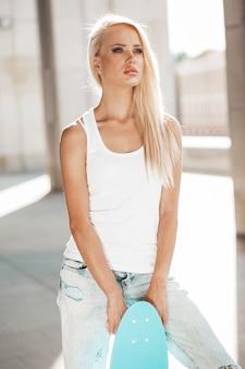 Portret piękna śliczna blond dziewczyna w białej koszulce i cajgach pozuje outdoors. dziewczyna z deskorolka niebieski grosz na ulicy