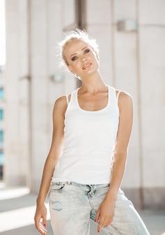 Portret piękna śliczna blond dziewczyna w białej koszulce i cajgach pozuje outdoors. śliczna dziewczyny pozycja na ulicznym tle