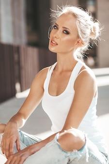 Portret piękna śliczna blond dziewczyna w białej koszulce i cajgach pozuje outdoors. śliczny dziewczyny obsiadanie na asfalcie na ulicie