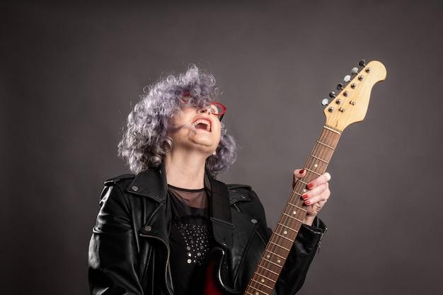 Portret piękna stara kobieta bawić się gitarę elektryczną