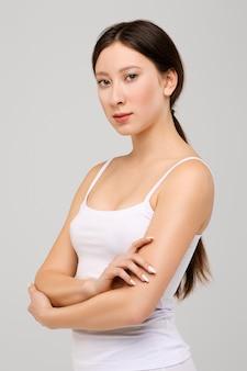 Portret piękna szczęśliwa azjatykcia dziewczyna z rękami składał na żołądku