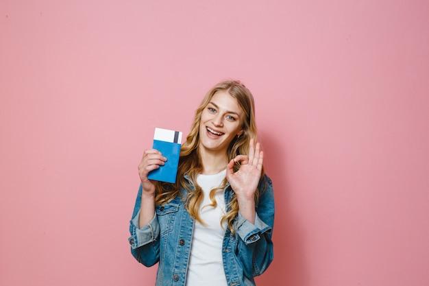 Portret piękna szczęśliwa dziewczyna odizolowywająca nad różowym tła mienia podróży biletami i paszportem