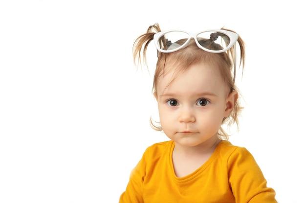 Portret piękna szczęśliwa mała dziewczynka w okularach przeciwsłonecznych na białym tle. widok z góry