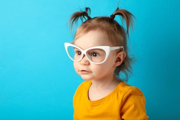 Portret piękna szczęśliwa mała dziewczynka w okularach przeciwsłonecznych na niebiesko z miejsca na kopię. widok z góry