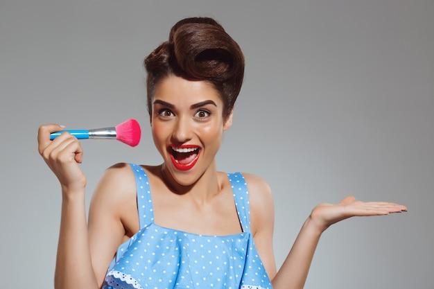 Portret piękna szpilki kobieta przy pracownianym mienie makijażu muśnięciem