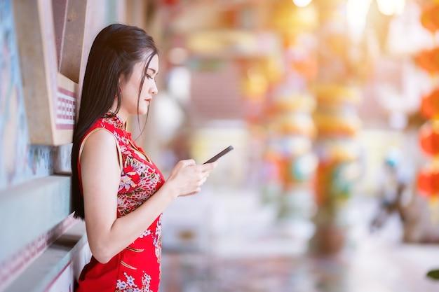 Portret piękna uśmiecha się azjatycka młoda kobieta ubrana w czerwony tradycyjny chiński cheongsam i pisze wiadomość na smartfonie z okazji chińskiego festiwalu noworocznego w chińskiej świątyni