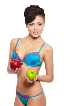 Portret piękna uśmiechnięta brunetki kobieta w białej bieliźnie z zieloną i czerwoną jabłczaną dietą odizolowywającą na bielu
