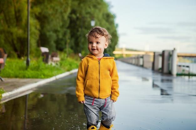 Portret piękna uśmiechnięta dzieciak chłopiec. szczęśliwe dziecko przed zielonym drzewem. dziecko bawi się na zewnątrz. roześmiany zdrowy chłopiec w żółtym płaszczu przeciwdeszczowym