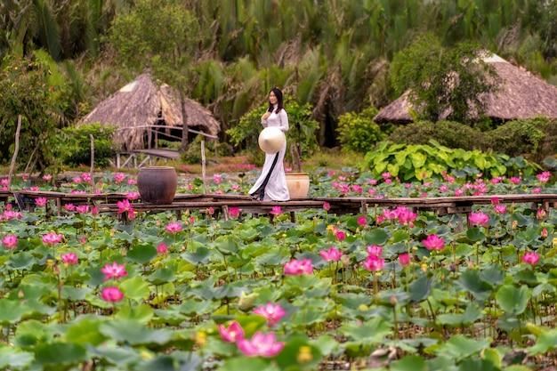Portret piękna wietnamczyk kobieta z tradycyjnym wietnamskim kapeluszem trzyma różowego lotosu
