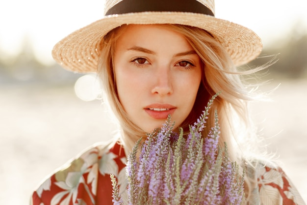 Portret piękna z bliska piękna romantyczna blond dziewczyna, ciesząc się doskonałym zapachem lawendy. koncepcja pielęgnacji skóry i kosmetyków. ciepłe kolory zachodu słońca.