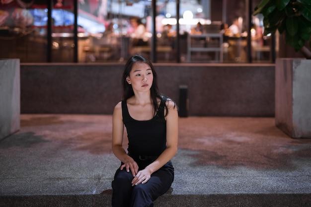 Portret piękne azjatyckie kobiety siedzącej na zewnątrz w nocy