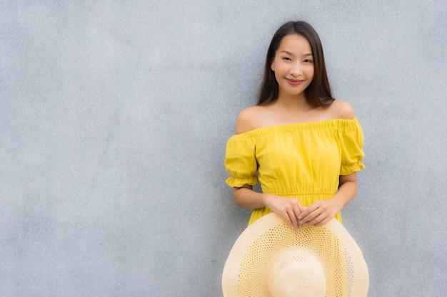 Portret piękne azjatykcie kobiety one uśmiechają się szczęśliwego z betonowym tłem