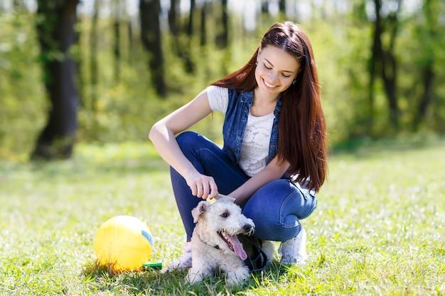Portret piękne kobiety czesanie jej psa na zewnątrz