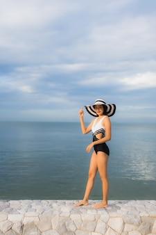 Portret piękne młode azjatykcie kobiety relaksują uśmiech szczęśliwego wokoło morze plaży oceanu