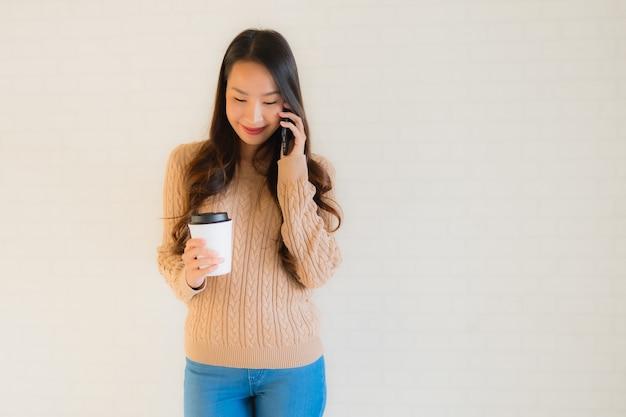 Portret piękne młode azjatykcie kobiety uśmiechają się szczęśliwego use mobilnego mądrze telefon