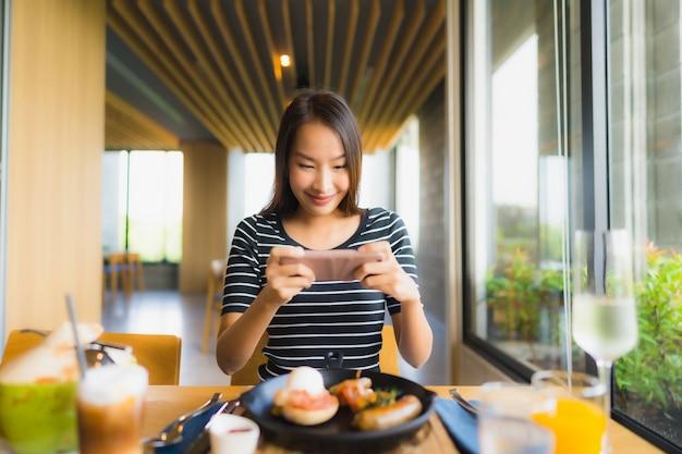 Portret piękne młode azjatykcie kobiety uśmiechają się szczęśliwego w restauraci i sklep z kawą kawiarni