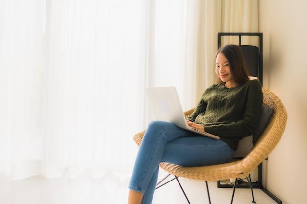 Portret piękne młode azjatykcie kobiety używa komputer lub laptop dla pracować i siedzieć na kanapy krześle