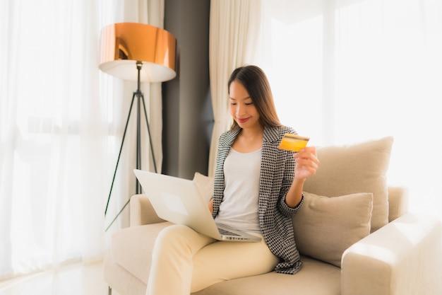 Portret piękne młode azjatykcie kobiety używa komputerowego laptop lub mądrze i telefon komórkowy z kredytową kartą dla online zakupy