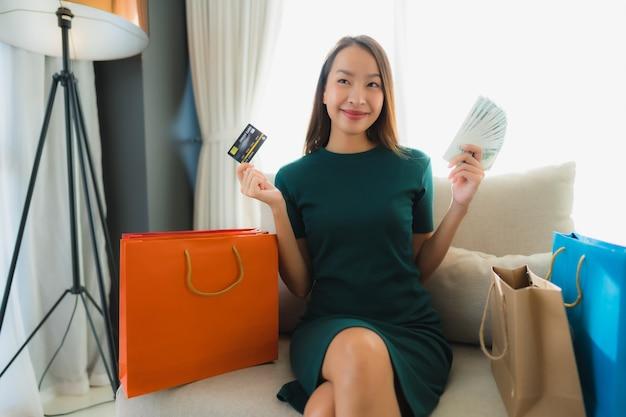 Portret piękne młode azjatykcie kobiety używa kredytową kartę dla online zakupy