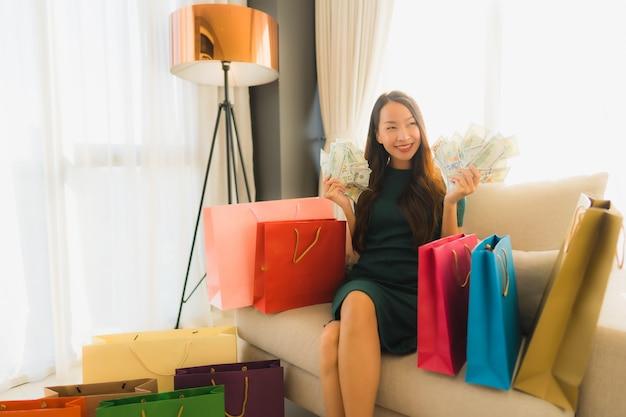 Portret piękne młode azjatykcie kobiety używa pieniądze