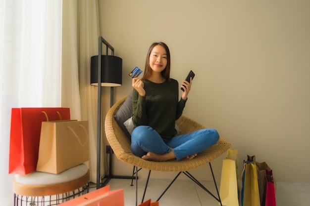 Portret piękne młode azjatykcie kobiety używa telefon komórkowego z kredytową kartą dla online zakupy