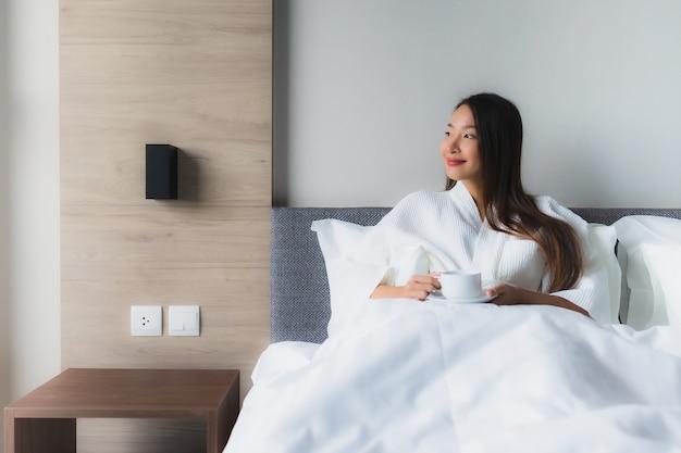 Portret piękne młode azjatykcie kobiety z filiżanką na łóżku