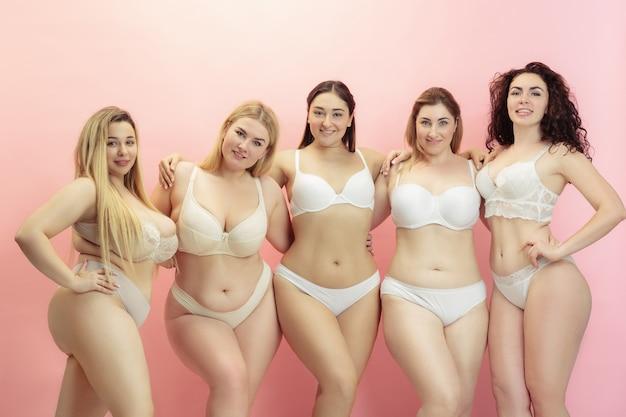 Portret piękne plus size młodych kobiet pozowanie na różowo