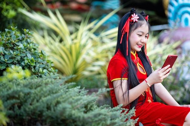 Portret piękne uśmiechy cute little asian dziewczyna ubrana w czerwony tradycyjny chiński cheongsam i pisanie wiadomości na smartfonie