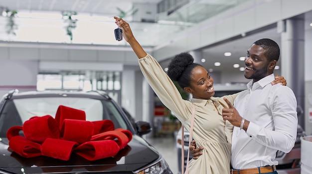 Portret pięknego afrykańskiego małżeństwa przyszedł do salonu, aby kupić swój pierwszy rodzinny samochód