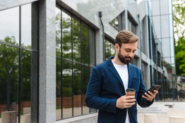 Portret pięknego biznesmena w kurtce trzymającego telefon komórkowy, stojąc na zewnątrz w pobliżu budynku z kawą na wynos