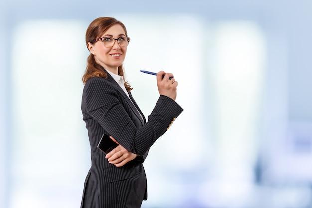 Portret pięknego bizneswomanu 50 uszu starych z telefonem komórkowym i piórem w biurze.
