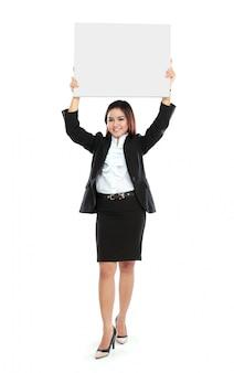 Portret pięknego bizneswomanu mienia pusty plakat nad jej głową