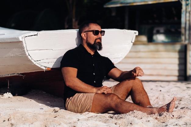 Portret pięknego brutalnego mężczyzny, cieszącego się i relaksującego, siedzącego na plaży na wyspie mauritius. mężczyzna na plaży le morne w czarnych ubraniach i okularach. tropikalna plaża.