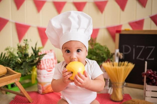 Portret pięknego chłopca w białym kapeluszu szefa kuchni, jedzenie jabłka