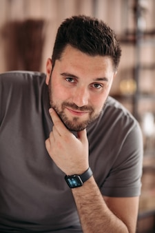 Portret pięknego kaukaskiego mężczyzny o ciemnych włosach, brązowych oczach i brodzie w szarej koszulce patrzącej w kamerę