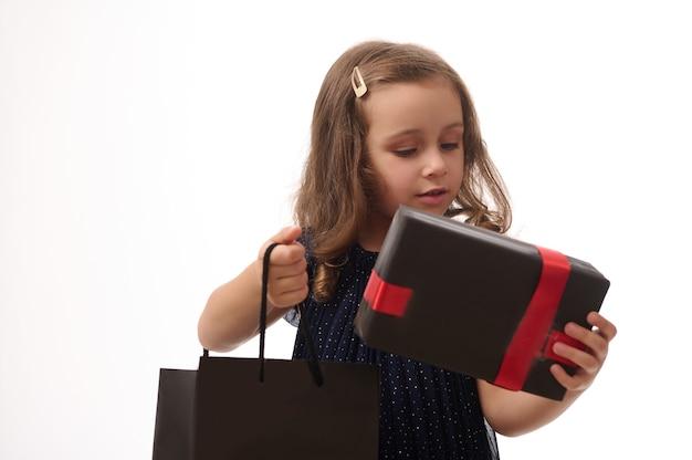 Portret pięknej 4 letniej dziewczynki z zamkniętymi oczami, trzymającej pakiet prezentów i zakupów, pozowanie na białym tle z miejsca na kopię. koncepcja czarnego piątku
