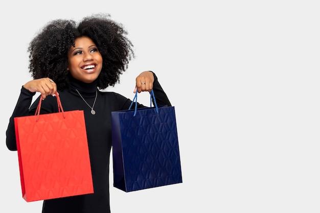 Portret pięknej afro uśmiechniętej dziewczyny trzymającej torby na zakupy na szarym tle