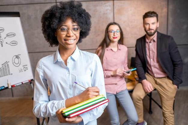 Portret pięknej afrykańskiej bizneswoman trzymającej kolorowe książki w biurze ze współpracownikami w tle