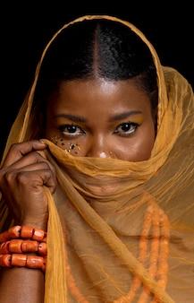 Portret pięknej afrykańskiej kobiety noszącej tradycyjne akcesoria i żółtą zasłonę