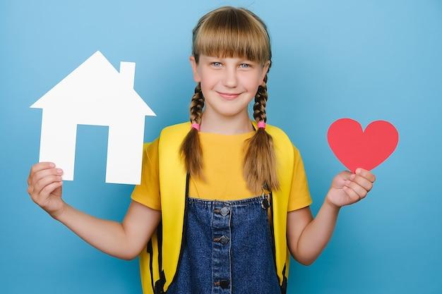 Portret pięknej atrakcyjnej uśmiechniętej uczennicy trzymającej małe czerwone serce i papierowy model białego domu, szczęśliwy patrząc na kamerę, nosi żółty plecak, na białym tle nad niebieskim kolorem tła w studio